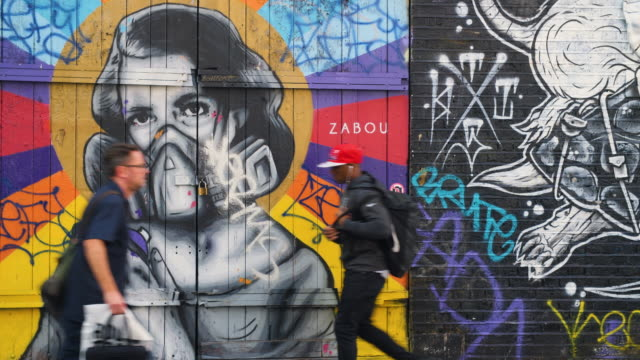 people pass colourful street art on brick lane, london - luftverschmutzung stock-videos und b-roll-filmmaterial