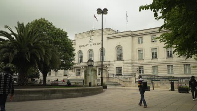 people pass hackney town hall, london - hackney stock-videos und b-roll-filmmaterial