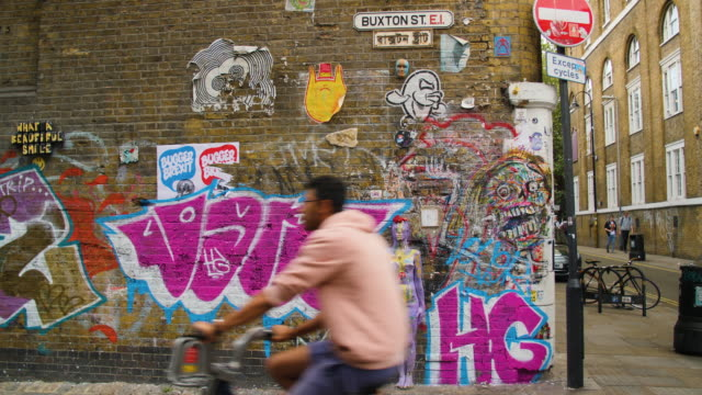 people pass in front of a brick wall adorned with graffiti and street art - city life stock videos & royalty-free footage