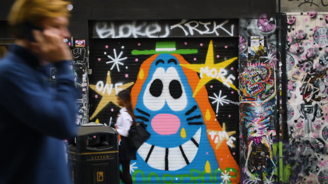 people pass in front of brightly coloured street art on brick lane, london - street style点の映像素材/bロール