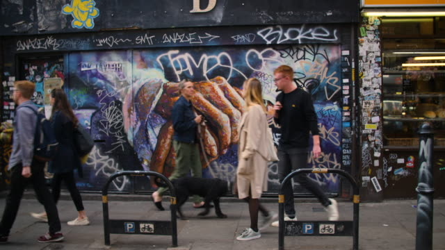People pass in front of street art by Mick Taylor, Brick Lane