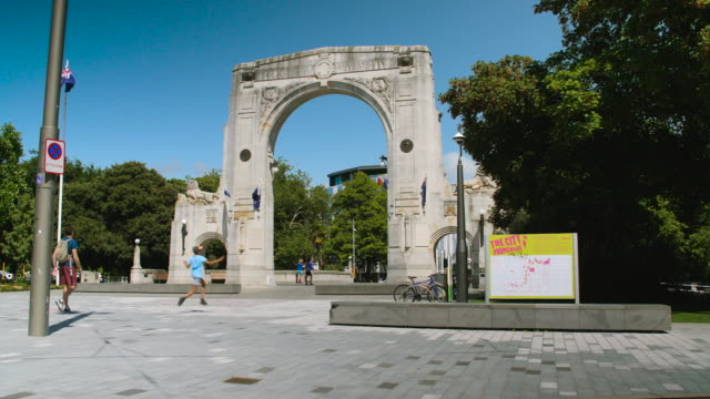 People pass in front of the Bridge of Remembrance, Christchurch
