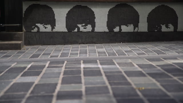 vidéos et rushes de people pass tile artwork of the beatles, liverpool - sculpture production artistique