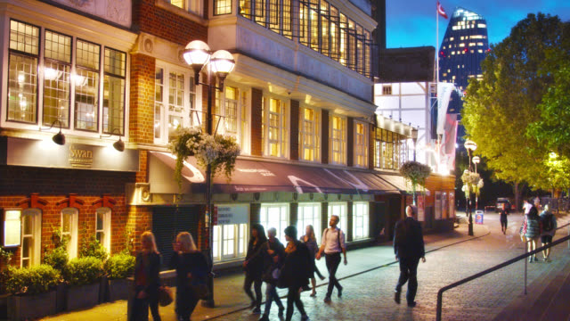 people passing by boutique stores on a london street in night - store opening stock videos & royalty-free footage