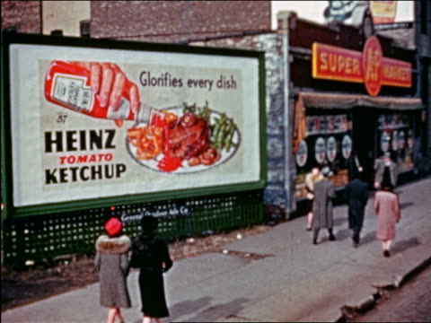 1941 people passing Heinz tomato ketchup billboard next to grocery store / Chicago / industrial