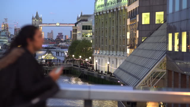 People passing London Bridge at rush hour with Tower Bridge in the back ground.