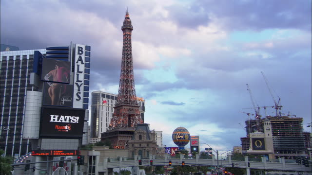 ws people passing over footbridge in front of eiffel tower replica in front of paris hotel at dusk/ las vegas, nevada - replica della torre eiffel video stock e b–roll