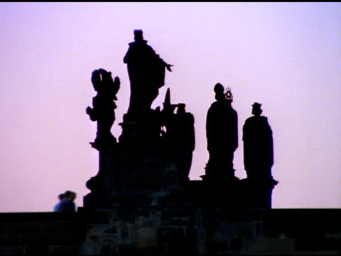people passing silhouetted statues on charles bridge, prague - charles bridge stock videos & royalty-free footage
