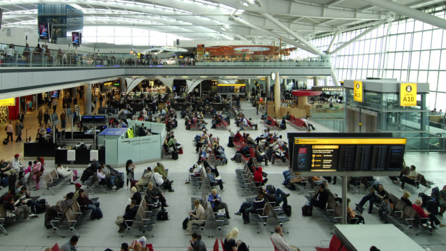 t/l wa ha people passing through a large terminal / london - flughafen stock-videos und b-roll-filmmaterial