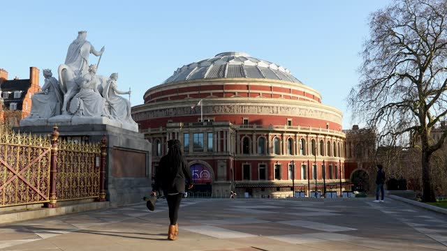 vídeos de stock, filmes e b-roll de people passing through kensington gardens in front the royal albert hall with its 150th anniversary sign displayed on april 04, 2021 in london,... - royal albert hall