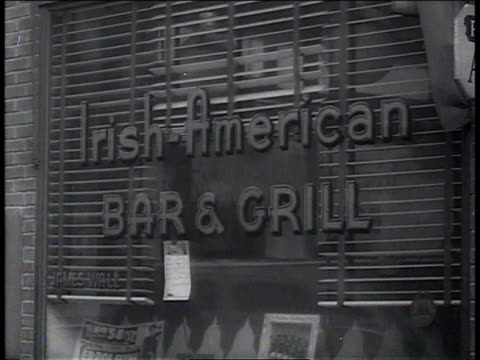 1941 CU people passing window with the sign Irish American Bar & Grill / Brooklyn, New York, United States