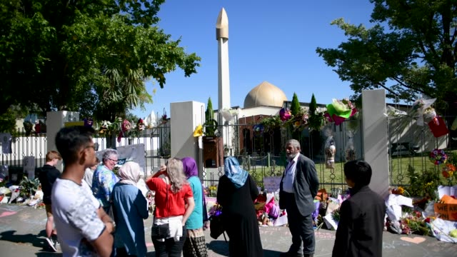 people pause next to flowers and tributes outside al noor mosque on march 24 2019 in christchurch new zealand 50 people were killed and dozens were... - christchurch stock-videos und b-roll-filmmaterial