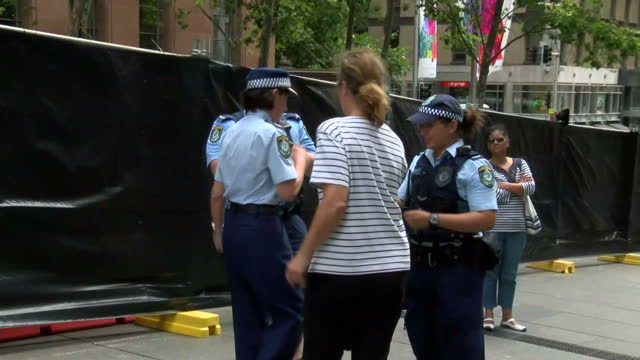 people pay respects for victims held at lindt cafe in sydney siege shows exterior shots of police officers standing guard outside the lindt cafe... - bankräuber stock-videos und b-roll-filmmaterial