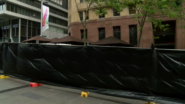 vidéos et rushes de people pay respects for victims held at lindt cafe in sydney siege. shows exterior shots of the cordon surrounding the lindt cafe on december 16,... - braqueur de banque