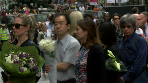 vidéos et rushes de people pay their respects for the victims held at the lindt cafe during sydney siege. shows exterior shots of crowds queuing to lay flowers in memory... - braqueur de banque