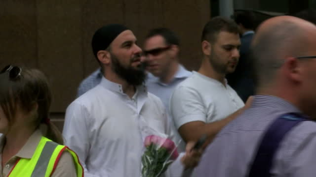 people pay their respects for victims held at lindt cafe in sydney siege shows exterior shots of muslim men holding flowers at memorial site on... - bankräuber stock-videos und b-roll-filmmaterial