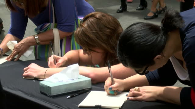 vidéos et rushes de people pay their respects to the victims who were held at lindt cafe during the sydney siege. shows exterior shots of people signing books of... - braqueur de banque