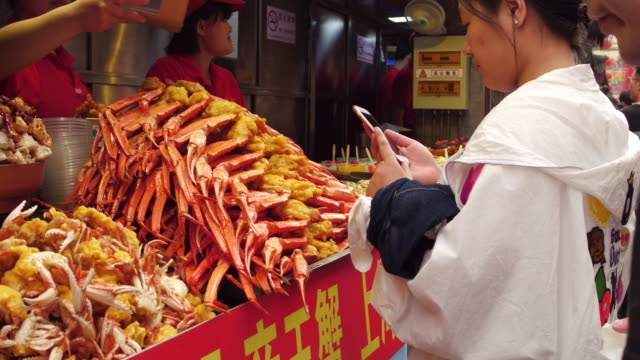 People pay with QR code in famous Wangfujing Snack Street on May 4 2017 in Beijing China Wangfujing is a main business street for tourism next to the...