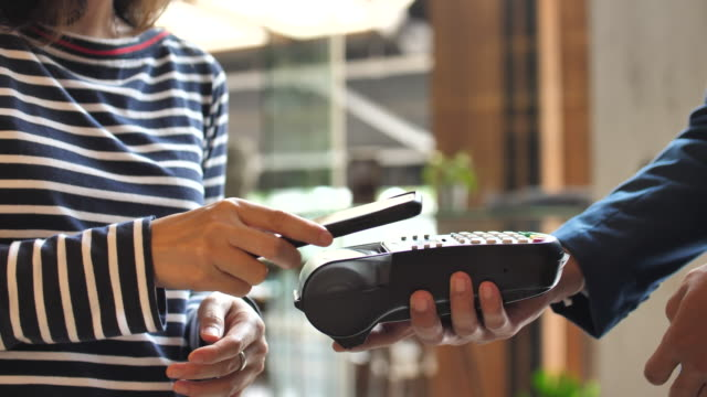 people paying contactless payment with mobile phone in a shop - electronic banking stock videos & royalty-free footage