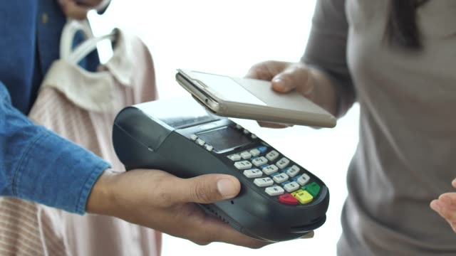 people paying contactless payment with smartphone - electronics store stock videos & royalty-free footage