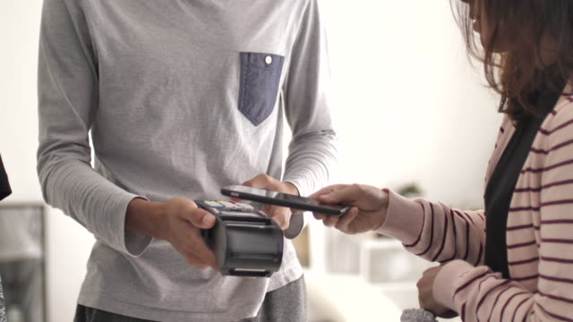 people paying with mobile phone contactless payment in store - radio frequency identification stock videos & royalty-free footage