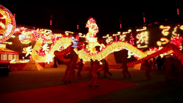 ms ts people performing dragon dance at city wall new year lantern festival  audio  / xi'an, shaanxi, china - drache stock-videos und b-roll-filmmaterial