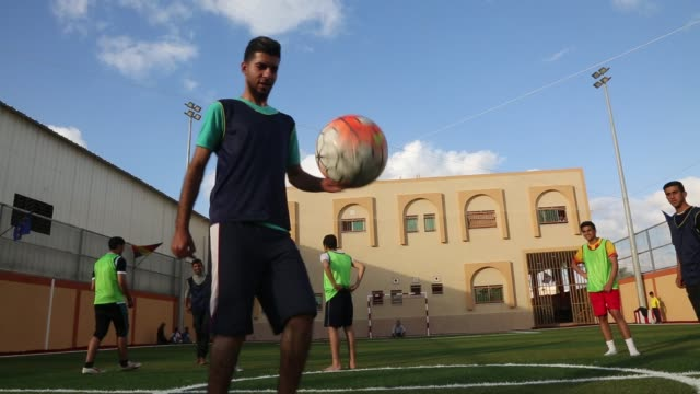 vidéos et rushes de people play at soccer in an artificial grass spreading camp in many neighborhoods in the gaza strip on march 3 2019 - turf
