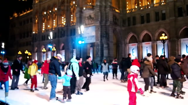 People play ice skating at night outside.