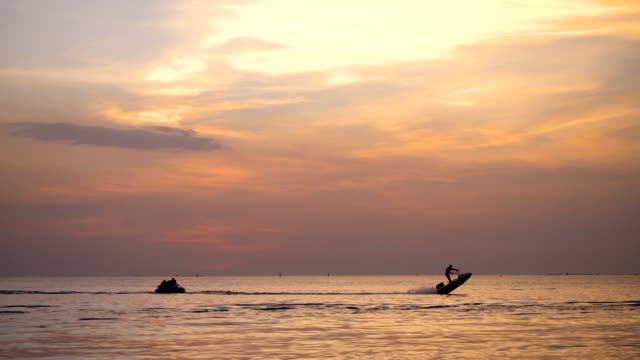 people playing banana boat at sunset. - pattaya stock videos & royalty-free footage