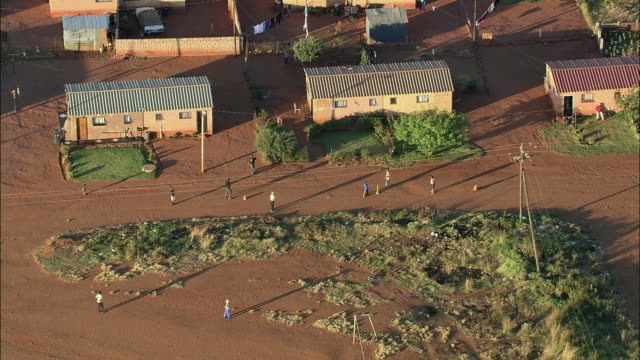 vidéos et rushes de aerial ws zi people playing cricket game on dirt road in town, johannesburg, gauteng, south africa - cahute