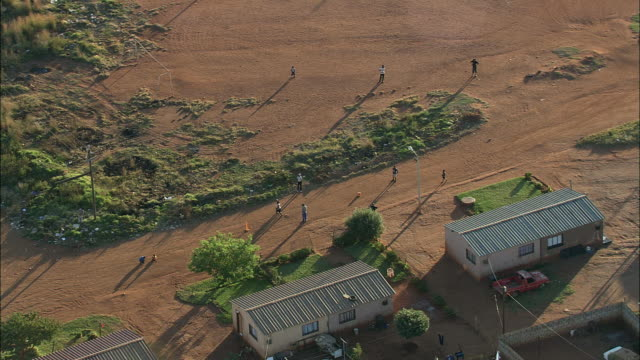 vidéos et rushes de aerial ws zo people playing cricket game on dirt road in town, johannesburg, gauteng, south africa - cahute