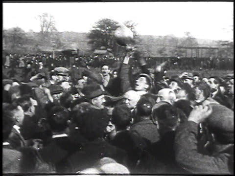 1930 montage people playing football in annual shrovetide match / ashbourne, england - 1930 stock-videos und b-roll-filmmaterial