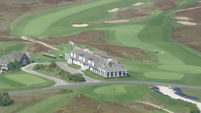 ws aerial zo pan zi people playing golf at golf course by ram island / new york, united states - golf grass stock videos & royalty-free footage