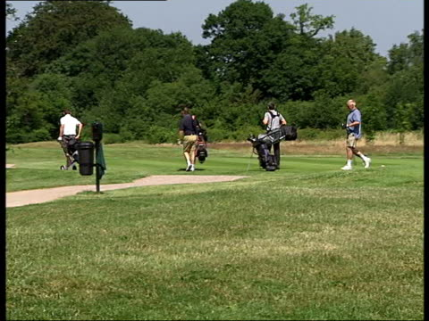 people playing golf at surrey downs golf club england surrey surrey downs golf club ext general view of surrey downs golf course / back view group of... - golf bag stock videos and b-roll footage