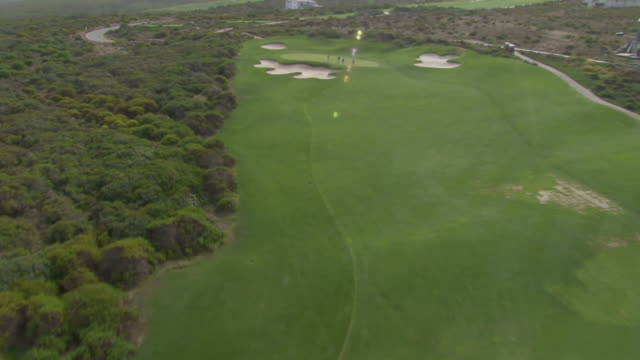 ws aerial td ds people playing golf on golf course / western cape, south africa - green golf course stock videos and b-roll footage