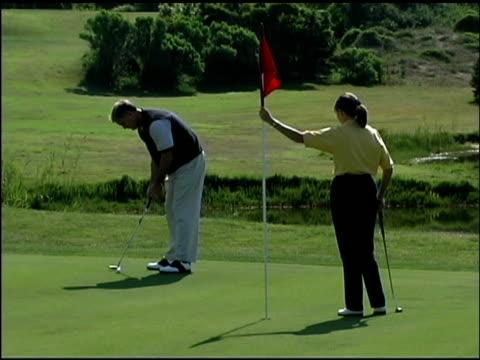 vídeos y material grabado en eventos de stock de people playing golf - bandera de golf