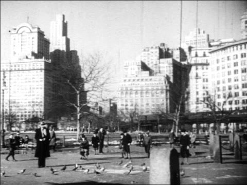 b/w 1930 people playing in city park as elevated train goes by in background / new york city / newsreel - 1930 stock-videos und b-roll-filmmaterial