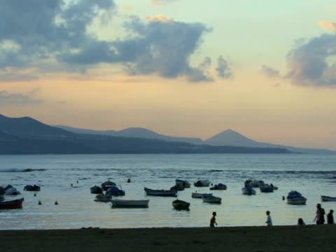 ws people playing on beach near anchored rowboats floating on ocean / las palmas de gran canaria, spain - グランカナリア点の映像素材/bロール