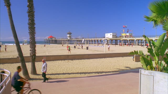 WS People playing on beach, pier in background / Huntington Beach, California, USA
