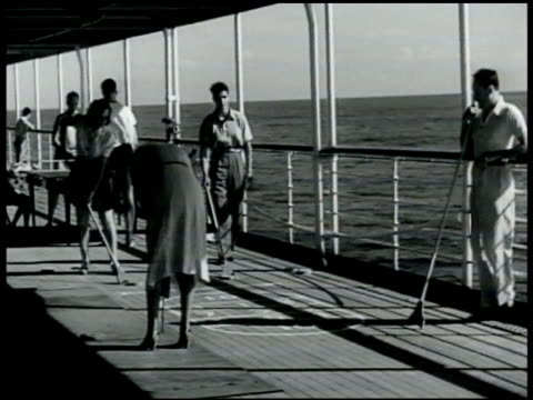 vídeos de stock e filmes b-roll de people playing shuffle board on deck of cruise ship. middle-aged male & female relaxing in deck chairs hers covered. people sitting at tables around... - 1949