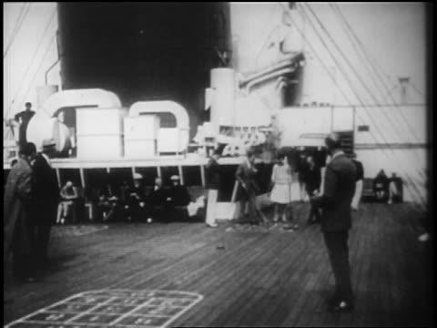 b/w 1928 people playing shuffleboard on deck of ocean liner / newsreel - 1928 stock-videos und b-roll-filmmaterial