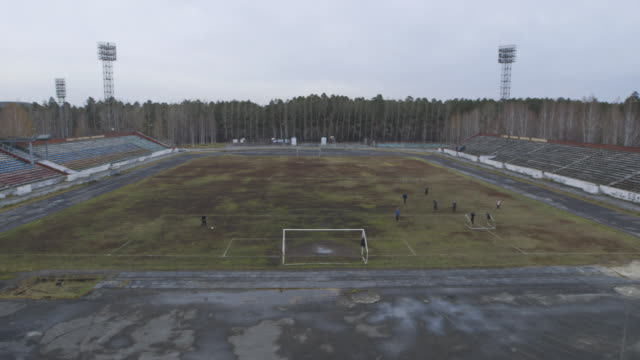 people playing soccer in asbest stadium, extreme wide shot - football pitch stock videos & royalty-free footage