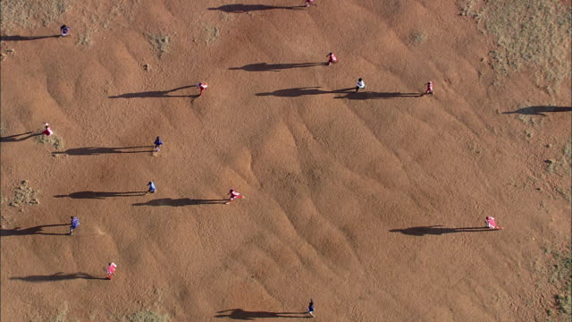 AERIAL WS People playing soccer on red earth pitch, Johannesburg, Gauteng, South Africa
