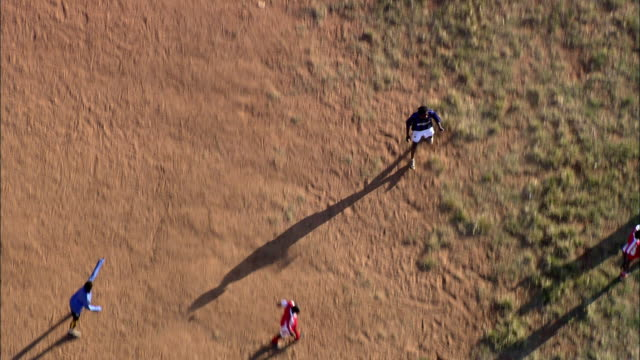 aerial ms zo ws people playing soccer on red earth pitch, johannesburg, gauteng, south africa - zoom out stock videos & royalty-free footage
