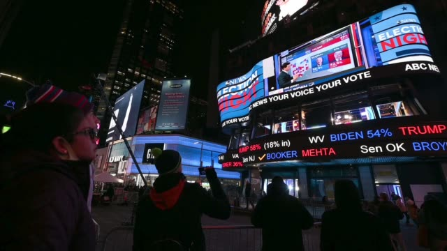 people point to election results on large digital screens in times square on november 03, 2020 in new york city. after a record-breaking early voting... - joe 03 stock videos & royalty-free footage