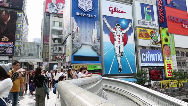 People pose for a selfie photograph using a smartphone while standing in front of an advertisement for Ezaki Glico Co center in the Dotonbori...