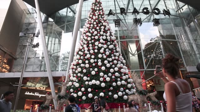 people pose for photographs next to a christmas tree outside the paragon shopping mall on orchard road in singapore, on sunday, dec. 16 close up,... - salvatore ferragamo stock videos & royalty-free footage