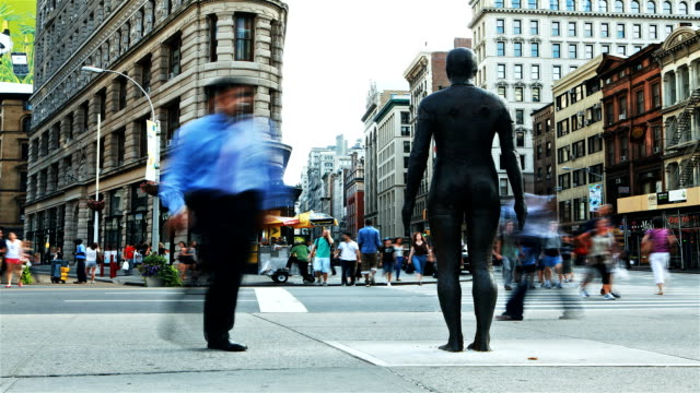 People pose for photos with a statue in front of the Flat Iron building in New York City.