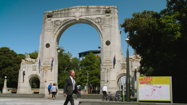 people pose in front of, and pass by, the bridge of remembrance, christchurch - new zealand culture stock videos and b-roll footage