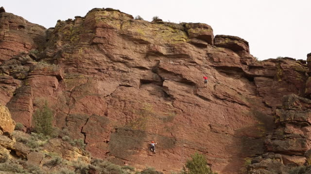 people practicing rock climbing inside of smith rock state park on a sunny day. - smith rock state park stock videos & royalty-free footage